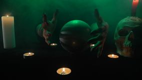 Τρομακτικός στενός επάνω της δημιουργίας μαγισσών σε μια σφαίρα κρυστάλλου, έναν πίνακα με τα κεριά και ένα κρανίο, καπνός φιλμ μικρού μήκους