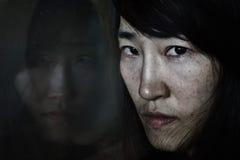 Τρομακτικός της αντανάκλασης γυναικών ` s στον καθρέφτη που κοιτάζει στη γυναίκα Στοκ Φωτογραφία