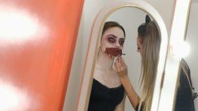 Τρομακτικό makeup για να γιορτάσει αποκριές Ένα κορίτσι με ένα στόμα που ράβεται επάνω Η αντανάκλαση στον καθρέφτη Το όμορφο κορί απόθεμα βίντεο