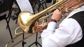 Τρομπόνι παιχνιδιού μουσικών ατόμων στη δημοτική ορχήστρα που αποδίδει στη συναυλία υπαίθρια απόθεμα βίντεο