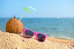 Τροπικά καρύδα και γυαλιά ηλίου στην παραλία Στοκ Εικόνες