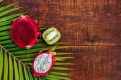 Τροπικά φρούτα στο μαύρο ξύλινο υπόβαθρο στοκ εικόνες
