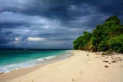 Τροπική αμμώδης παραλία με έναν δραματικό ουρανό πριν από μια θύελλα Στοκ Φωτογραφία