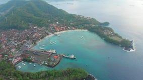 Τροπική παραλία και από το Μπαλί πόλη με το λιμένα και το σκάφος και τον μπλε ωκεανό εναέρια όψη απόθεμα βίντεο