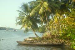 Τροπικοί ποταμοί της Ινδίας Γραφικός που κλίνεται πέρα από τους φοίνικες νερού, στενή βάρκα πιρογών στοκ εικόνες