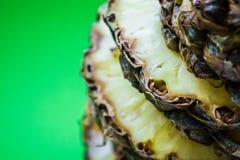 Τροπικό εσπεριδοειδές ο ανανάς που κόβεται στα δαχτυλίδια σε ένα πράσινο υπόβαθρο r Εξωτικός του καλοκαιριού στοκ εικόνες