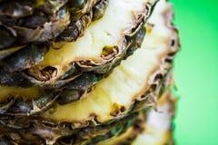 Τροπικό εσπεριδοειδές ο ανανάς που κόβεται στα δαχτυλίδια σε ένα πράσινο υπόβαθρο r Εξωτικός του καλοκαιριού στοκ εικόνα