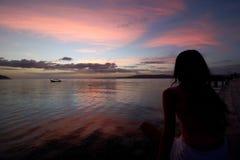 Τροπικό ηλιοβασίλεμα στο αρχιπέλαγος raja ampat με το νέο silho γυναικών Στοκ Εικόνα