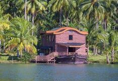 Τροπικό σπίτι υπό μορφή σκάφους δίπλα στη θάλασσα στη ζούγκλα με τους πράσινους φοίνικες Παραθαλάσσιο θέρετρο πολυτέλειας σε ένα  στοκ φωτογραφία