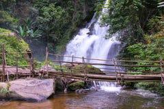 Τροπικό τοπίο τροπικών δασών με τις εγκαταστάσεις ζουγκλών, το ρέοντας νερό του καταρράκτη Pha Dok Xu και τη γέφυρα μπαμπού Mae K Στοκ Φωτογραφία