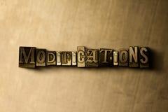 ΤΡΟΠΟΠΟΙΗΣΕΙΣ - κινηματογράφηση σε πρώτο πλάνο της βρώμικης στοιχειοθετημένης τρύγος λέξης στο σκηνικό μετάλλων Στοκ Φωτογραφία