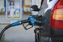Τροφοδοτώντας με καύσιμα το ακροφύσιο που παρεμβάλλεται στη δεξαμενή αερίου του αυτοκινήτου Στοκ Φωτογραφία