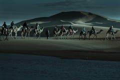 Τροχόσπιτο των τουριστών που περνούν τη λίμνη ερήμων στις καμήλες στοκ εικόνα με δικαίωμα ελεύθερης χρήσης