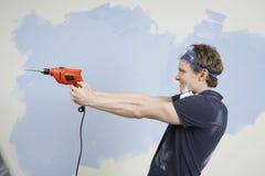 Τρυπάνι εκμετάλλευσης ατόμων ως πυροβόλο όπλο ενάντια στον τοίχο Στοκ φωτογραφίες με δικαίωμα ελεύθερης χρήσης