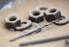 Τρυπάνι και μερικά καρύδια και δαχτυλίδια συσκευασίας στοκ φωτογραφίες