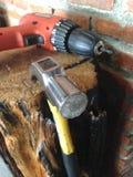 Τρυπάνι και σφυρί στο ξύλινο κούτσουρο στοκ φωτογραφίες