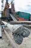 Τρυπάνι πετρελαίου ενάντια στο σκηνικό της γεώτρησης Στοκ Εικόνες