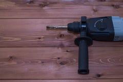 Τρυπάνι σφυριών σε ένα ξύλινο υπόβαθρο Κινηματογράφηση σε πρώτο πλάνο Το ηλεκτρικό εργαλείο Στοκ φωτογραφία με δικαίωμα ελεύθερης χρήσης