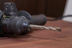 Τρυπάνι σφυριών σε ένα ξύλινο υπόβαθρο Κινηματογράφηση σε πρώτο πλάνο Το ηλεκτρικό εργαλείο Στοκ φωτογραφίες με δικαίωμα ελεύθερης χρήσης