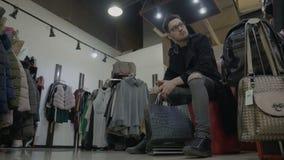 Τρυπημένες μοντέρνες τσάντες αγορών εκμετάλλευσης ατόμων και αναμονή τη φίλη της για να προσπαθήσει στα ενδύματα σε μια λεωφόρο κ φιλμ μικρού μήκους