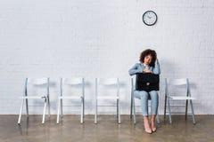Τρυπημένη γυναίκα με τη συνεδρίαση χαρτοφυλάκων στην καρέκλα στοκ εικόνες