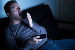 Τρυπημένη τηλεόραση προσοχής ατόμων τη νύχτα στοκ εικόνα