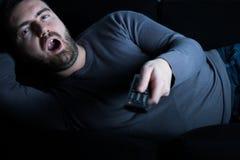 Τρυπημένη τηλεόραση προσοχής ατόμων τη νύχτα στοκ φωτογραφία με δικαίωμα ελεύθερης χρήσης