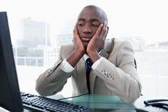 Τρυπημένος επιχειρηματίας που εξετάζει τον υπολογιστή του Στοκ Εικόνες