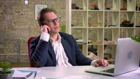 Τρυπημένος και απασχολημένος με στο καυκάσιο αρσενικό μιλά πέρα από το τηλέφωνο και κάθεται στην κίνηση στην αρχή φιλμ μικρού μήκους