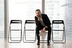 Τρυπημένος νεαρός άνδρας στη συνεδρίαση κοστουμιών στη αίθουσα αναμονής Στοκ εικόνες με δικαίωμα ελεύθερης χρήσης