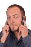 Τρυπημένος πολυάσχολος τύπος με δύο κινητά τηλέφωνα Στοκ Εικόνες