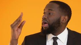 Τρυπημένο αφροαμερικανός άτομο στο κοστούμι που παρουσιάζει σημάδι αερολογιών αερολογιών, ανεπιτυχής διαπραγμάτευση απόθεμα βίντεο
