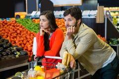 Τρυπημένο ζεύγος με το καροτσάκι αγορών στο οργανικό τμήμα Στοκ εικόνες με δικαίωμα ελεύθερης χρήσης