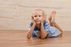Τρυπημένο μικρό κορίτσι που βρίσκεται στο ξύλινο πάτωμα Στοκ εικόνα με δικαίωμα ελεύθερης χρήσης