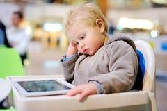 Τρυπημένο μικρό παιδί με μια ψηφιακή ταμπλέτα Στοκ Εικόνες