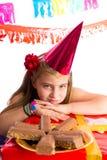 Τρυπημένο ξανθό κορίτσι παιδιών στο κόμμα με τις σοκολάτες Στοκ Φωτογραφία