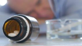Τρυπημένο πρόσωπο που φαίνεται απογοητευμένο στα ιατρικά χάπια και ένα καπνίζοντας τσιγάρο φιλμ μικρού μήκους