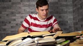 Τρυπώντας βιβλίο ανάγνωσης σπουδαστών ατόμων στη βιβλιοθήκη με πολλά βιβλία στο πανεπιστήμιο Σπουδαστής που αποθαρρύνεται ανάγνωσ απόθεμα βίντεο