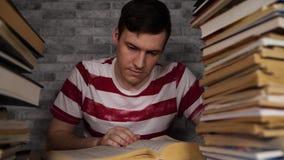 Τρυπώντας βιβλίο ανάγνωσης σπουδαστών ατόμων στη βιβλιοθήκη με πολλά βιβλία στο πανεπιστήμιο Σπουδαστής που αποθαρρύνεται ανάγνωσ φιλμ μικρού μήκους