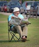 Τρυπώντας εφημερίδα της Κυριακής που διαβάζεται Στοκ φωτογραφία με δικαίωμα ελεύθερης χρήσης