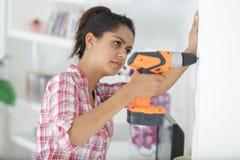 Τρυπώντας με τρυπάνι τοίχος γυναικών στο καινούργιο σπίτι στοκ φωτογραφίες