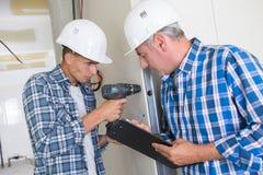 Τρυπώντας με τρυπάνι τοίχος εργατών οικοδομών μαθητευόμενων στοκ φωτογραφία