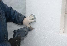 Τρυπώντας με τρυπάνι τοίχος οικοδόμων για την εγκατάσταση των αγκύρων για να κρατήσει τον άκαμπτο πίνακα αφρού μόνωσης στοκ φωτογραφίες
