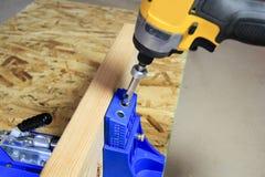 Τρυπώντας με τρυπάνι τρύπες τσεπών στο ξύλο που χρησιμοποιεί jig τρυπών τσεπών στοκ φωτογραφία με δικαίωμα ελεύθερης χρήσης