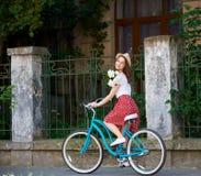 Τρυφερή νέα γυναίκα στο μπλε αναδρομικό ποδήλατο με τα peonies στοκ εικόνες με δικαίωμα ελεύθερης χρήσης