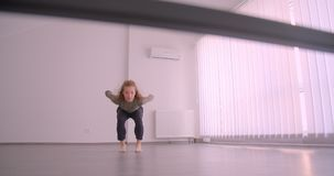 Τρυφερός καυκάσιος χορευτής που τεντώνει και που προετοιμάζει στην ελαφριά κατηγορία μπαλέτου φιλμ μικρού μήκους
