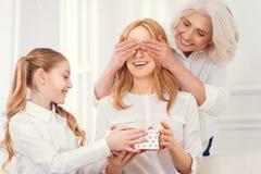 Τρυφερό δόσιμο κορών και grandma παρόν κατάπληκτος mom στοκ εικόνες με δικαίωμα ελεύθερης χρήσης