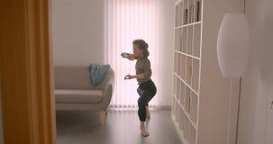Τρυφερό καυκάσιο ballerina prima που εκτελεί το σύγχρονο χορό στο ελαφρύ και άνετο δωμάτιο φιλμ μικρού μήκους
