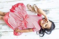 Τρυφερό κορίτσι που βρίσκεται δίπλα στις χρυσές παντόφλες της στοκ εικόνα με δικαίωμα ελεύθερης χρήσης