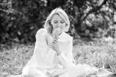 Τρυφερό ξανθό sniff κοριτσιών μικροσκοπικό λουλούδι ενώ καθίστε στο πράσινο λιβάδι χλόης Καθαρή και τρυφερή έννοια Η γυναίκα απολ στοκ φωτογραφίες με δικαίωμα ελεύθερης χρήσης